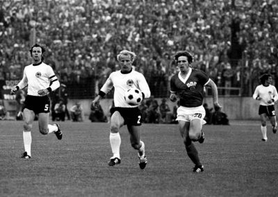 Match at the 1974 World Cup. L–R: West German players Franz Beckenbauer, Berti Vogts and in the background Wolfgang Overath, and East Germany's striker Martin Hoffmann (Photo: Rainer Mittelstädt, Wikimedia Commons).